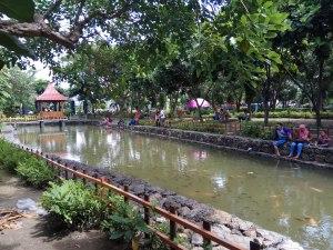 Pengunjung bisa bersantai sambil memberi makan ikan di kolam